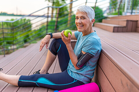 Older woman with yoga mat eating apple