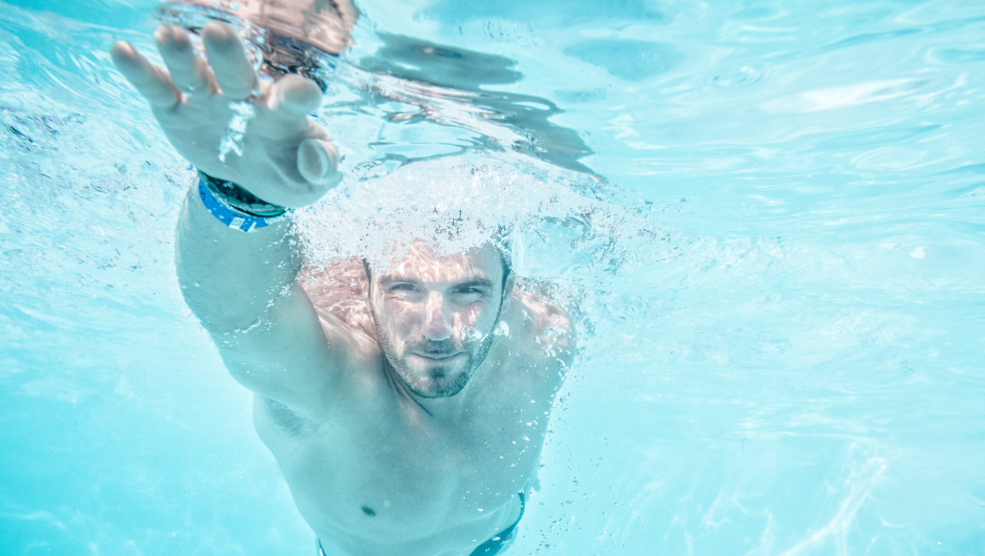 Man swimming in pool viewed from beneath